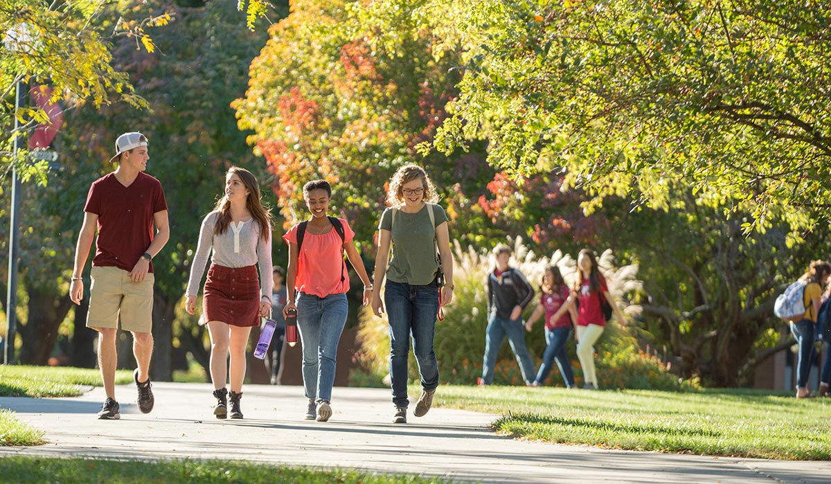 Four students walking on the Hesston College campus