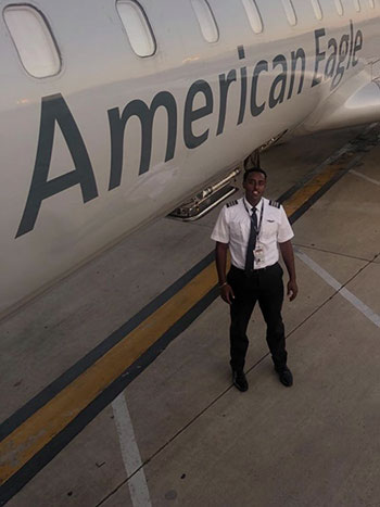 Ashenafi Tadese standing next to an American Eagle passenger plane