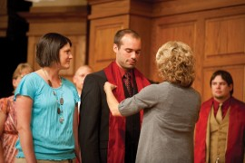 Faculty member Luann Yutzy places a stole on the shoulders of Pastoral Ministries graduate Dan Coburn of Accident, Md.