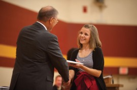 Kayci Detweiler of Kokomo, Ind., receives her Hesston College diploma from President Howard Keim at the college's centennial commencement.