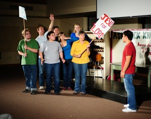 "Jesus, played by Omar Reyes (right) tests his followers' willingness to ""Follow me,"" in a sketch from the original play ""This is Your Pig."" Performers from left are Cody Zabroski, Jeron Baker, Rachel Brown, Ryan Kopper, Leah Baker, Anna Yoder and Margaret Wiebe."
