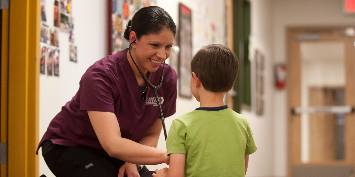 2016 Hesston College Nursing graduate Dra Aguilar (Wichita, Kan.) practices nursing skills on a young patient in this photo from 2015.