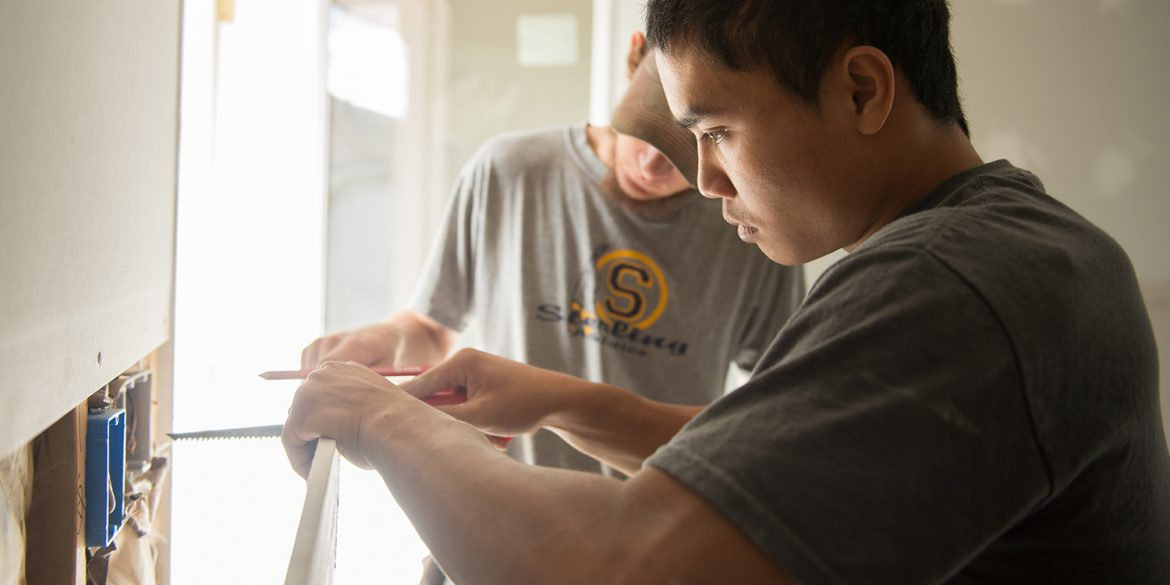 Levi Nofziger cuts drywall on a work day at a Habitat for Humanity house in Newton.