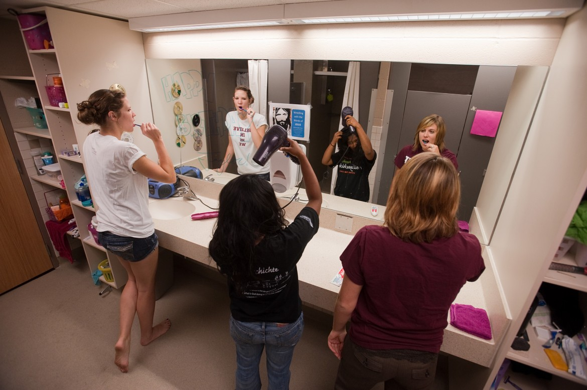 Hesston College students prepare for the day in a recently renovated bathroom in Erb Hall.