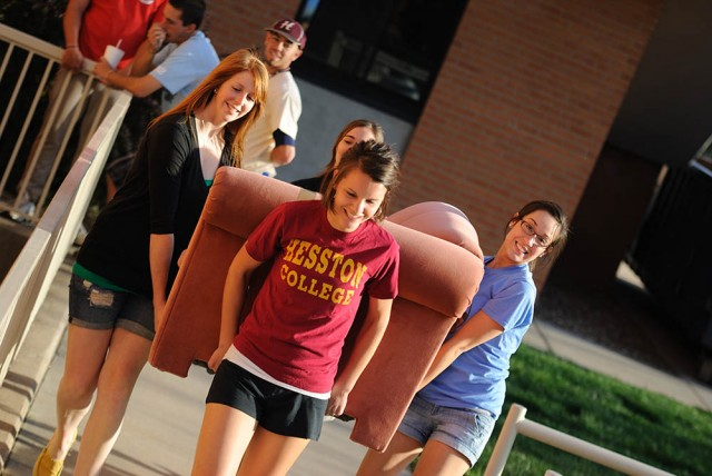 Students move furniture out from storage.