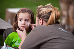 "A young festival-goer gets her face painted by sophomore Danielle Hanna of Whitewater, Kan., at Friday night's Tailgate Picnic and Family Festival. The evening's activities also included magic shows, a photo booth, kids activities and games and a ""Meet the Larks fall sports teams."""