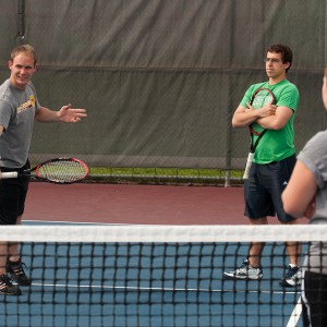 Hesston tennis coach Jeron Baker works with players