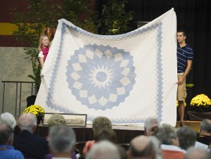Jessie Couch '07, Mulvane, Kan., and sophomore Chad Newcomer, Mount Joy, Pa., display a quilt for auction bidders.