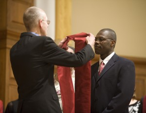 Hesston College Pastoral Ministries graduate Bernard Sejour receives a stole from program director David Greiser.
