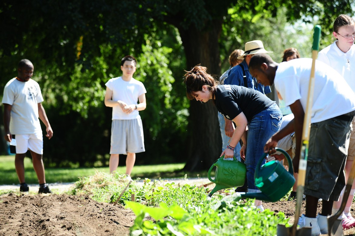 Dulaney Arzola of Stafford, Kan., and other students in the First Year Experience seminar work in the Intergenerational Community Garden. The garden is one of several projects the college employs in promoting sustainability on campus.