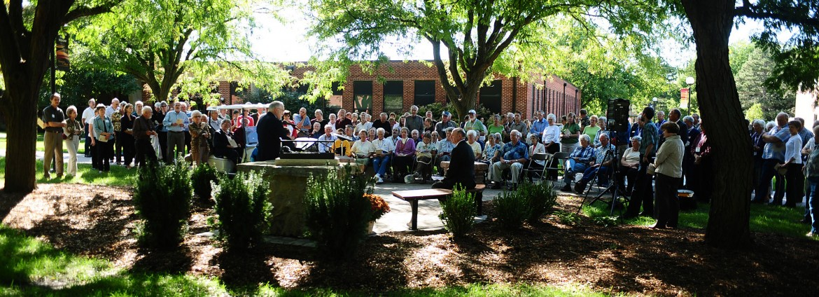 A crowd gathers to dedicate the Freedley Schrock memorial at Hesston College