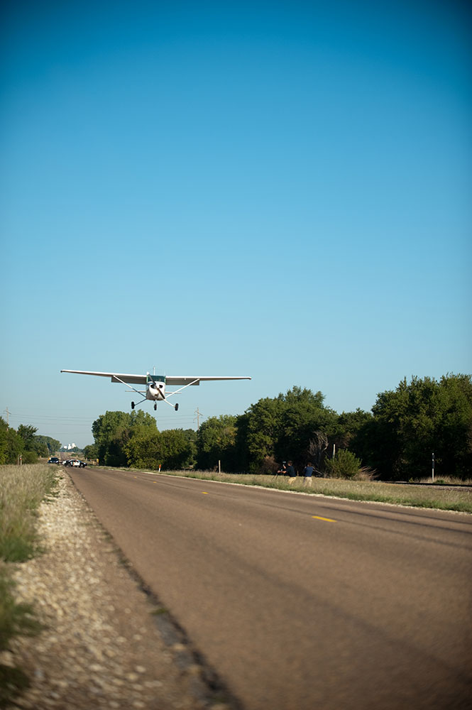 A Hesston College airplane, flown by instructor Travis Pickerill '99, prepares to land north of town on Old Highway 81. The plane was displayed on campus over the weekend.