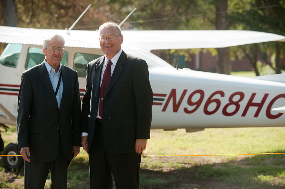 Former President Laban Peachey (1968 to 1980) and President Howard Keim pose with the Hesston College airplane with the radio call numbers in honor of President Peachey. Each of the college's five planes' call numbers includes the inauguration year of one of the presidents.