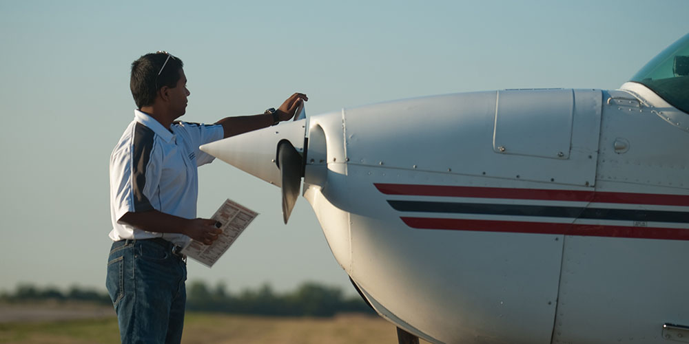 Hesston College sophomore Kush Lengacher prepares a plane for flight.