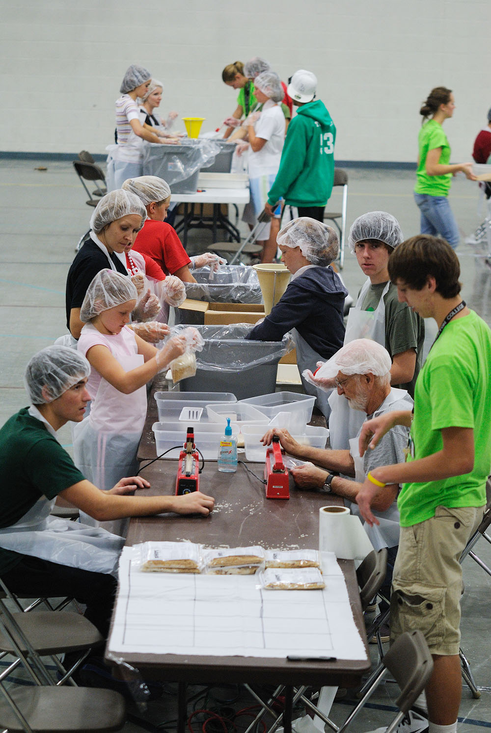 Hesston College students, faculty, staff and local community members came together to package more than 50,000 meals during Numana's food-packaging event Oct. 1. The project was the culminating event for the college's first No Impact Week. Pictured clockwise from left in the foreground: Scott Weaver (Goshen, Ind.), Rachel Teeter, staff member Angie Teeter, Collin Miller (Wellman, Iowa), Bible faculty Marion Bontrager and Alex Miller (Beemer, Neb.).