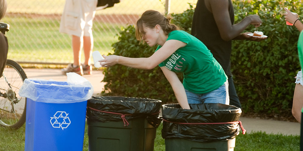 Hesston College sophomore Leah Mueller of Halstead, Kan., separates recyclables from trash during the college's September 2011 homecoming celebration.