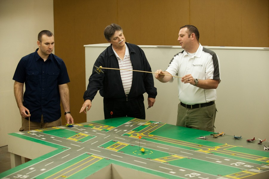 Jerry Holloman (left) and Jacob Gayer (right), members of Hesston College's first class of Air Traffic Control graduates in May 2011, work with Director of Aviation Dan Miller in the on-campus table model simulation lab.
