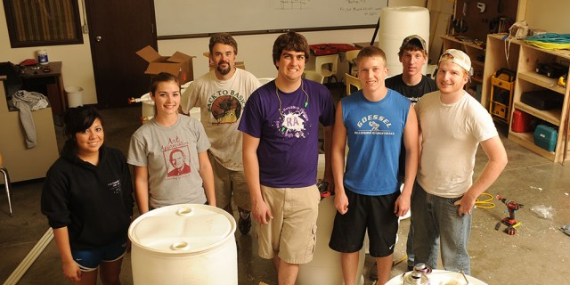 The Hesston College Entrepreneurship class takes a break from turning 55-gallon food-grade drums into rain barrels. Pictured from left are sophomores Brenda Nieto-Montoya (Three Rivers, Mich.), Mallory Schroeder (Newton, Kan.), business instructor David LeVan, Kyle Albrecht (Clarence, N.Y.) and Hayden Goerzen and freshmen Matt Weaver (Goshen, Ind.) and Brandon Sharkey (Goshen, Ind.). Class member not pictured is sophomore Miranda Hilliard (Sedgwick, Kan.).