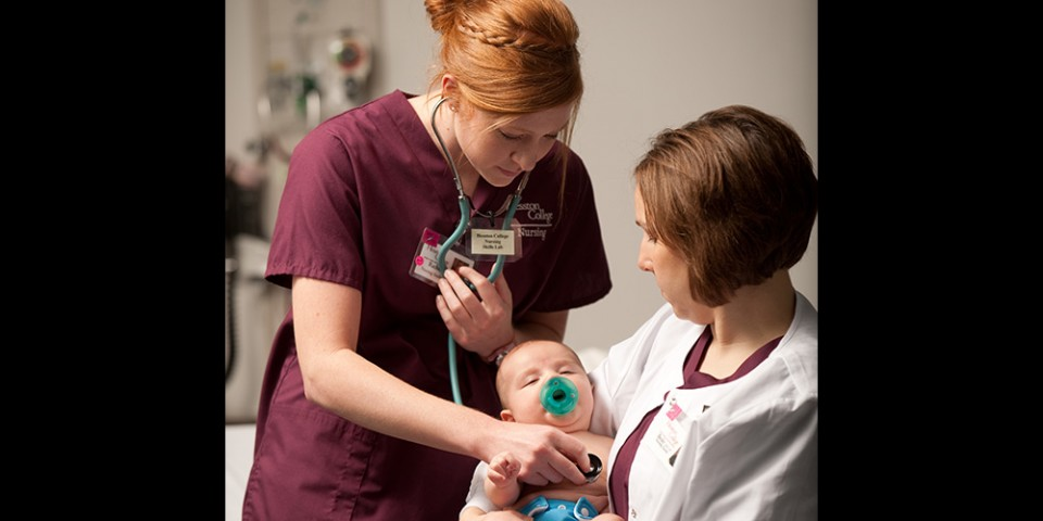 Hesston College nursing student Rachel Tippin (Newton, Kan.) listens to instructor Becky Bartell's son's heartbeat.