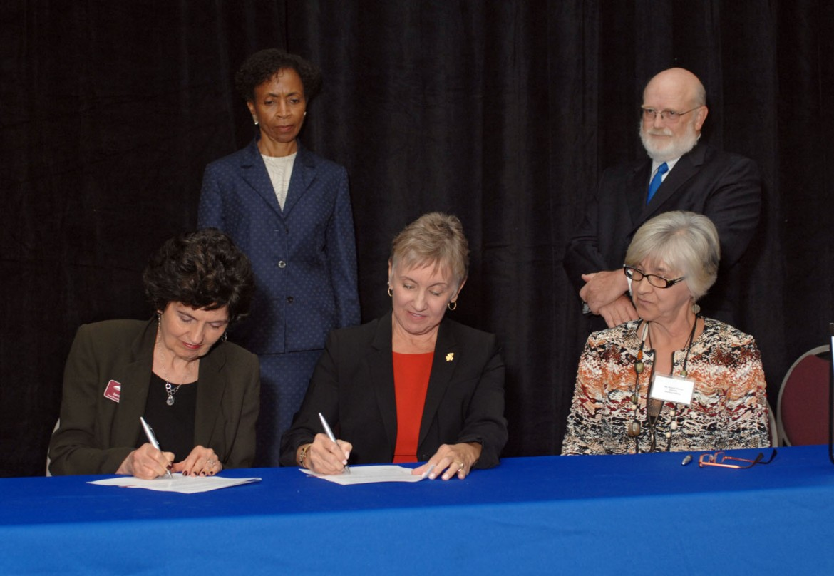 Dr. Sandra Zerger, Vice President of Academics at Hesston College, and Dean of the University of Kansas School of Nursing, Karen Miller, RN, Ph.D., FAAN, sign an articulation agreement for nurses who have earned their RN to earn a BSN through KU's online program on Sept. 11. Looking on are (standing) Bernadette Gray-Little, Ph.D., Chancellor of the University of Kansas; David Martin, RN, M.N., Clinical Associate Professor at the University of Kansas School of Nursing; and (seated) Bonnie Sowers, director of nursing at Hesston College.