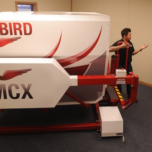 Hesston College Aviation program director Dan Miller (right) and flight instructor Travis Pickerill (center) get maintenance tips about the college's new Redbird MCX C182 G1000 GFC700 flight simulator.