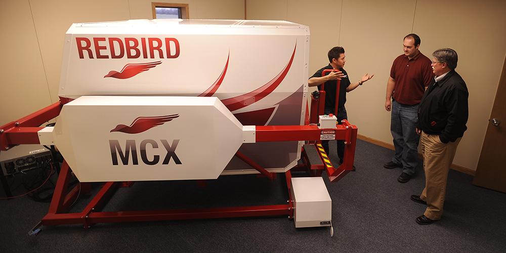 Hesston College Aviation program director Dan Miller (right) and flight instructor Travis Pickerill (center) get maintenance tips about the college's new Redbird MCX C182 G1000 GFC700 flight simulator.