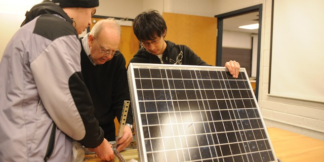 Physics students work with Dr. Nelson Kilmer on a solar energy project.