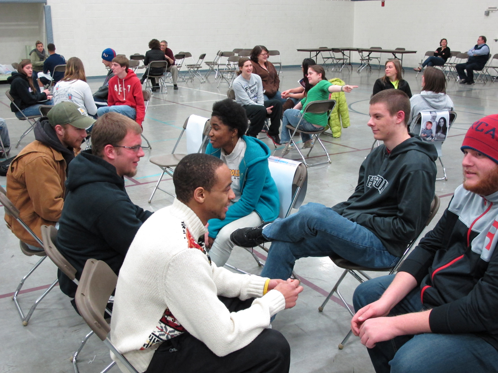 "Hesston College students work together in a ""family"" group to plan out their strategy for the week during a poverty simulation led by Harvey County Circles of Hope Wednesday night on the Hesston College campus. More than 100 students participated in the simulation. Pictured counter-clockwise from back left are freshman Jon Shetler (Hesston), sophomore Bonita Garber (Bainbridge, Pa.), freshman JD Hershberger (Hesston), sophomore Sam Ruth (Wichita, Kan.), freshman Christian Stevens (South Bend, Ind.) and freshman Jake Pokorney (Arnold, Mo.)"