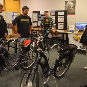 Hesston College physics students Keenan Jensen and Ron Wenger talk with Earth Day guests about the electric bicycles with solar power charging stations they helped build.