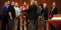 Pastoral ministries graduate Kenzie Intemann, Bessie, Okla., receives his stole and a blessing from program director Tim Lichti as he is surrounded by fellow pastoral ministries students, Bible and Ministry faculty, commissioning speaker Kurt Horst and President Howard Keim during pastoral ministries commissioning.