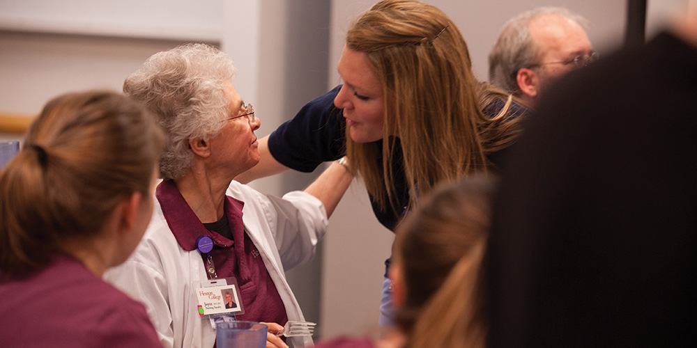 Nursing instructor Joyce Huber hugs a nursing alumna at a retirement break in Huber's honor.