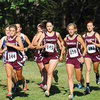 Hesston College women's cross country runs start a race.