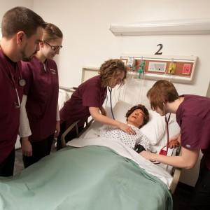 Hesston College Nursing students Chad Jones (Halstead, Kan.), Jennifer Kaberline (McPherson, Kan.), Brianne Stutzman (Hesston, Kan.) and Rinda Amstutz (Goessel, Kan.) practice on a sim patient in an on-campus nursing lab.