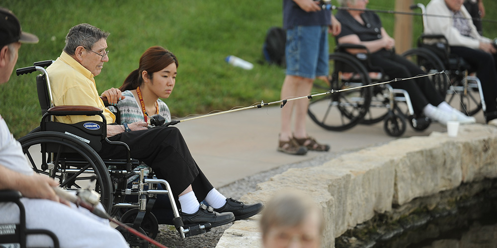 Hesston College freshman Misaki Murakami (Osaka, Japan) fishes with Schowalter Villa resident Allen Bitikofer at Lake Vista on Sept. 3 as part of Hesston College's Service Week.