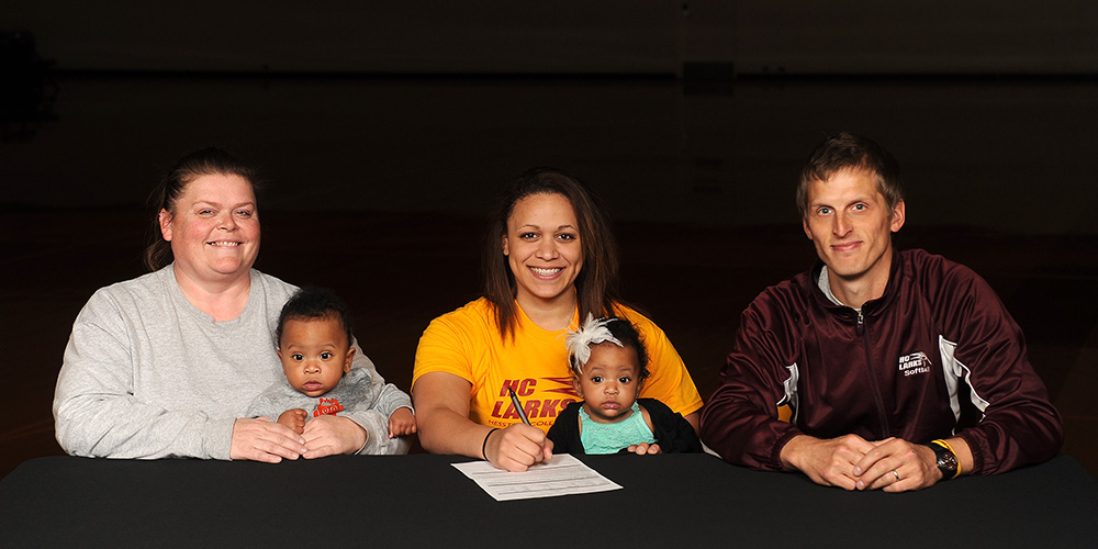 Kasee Tully (center), signs with Hesston Softball.