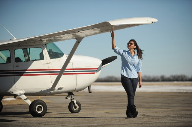 Megan inspects a Hesston College plane before a flight lesson.
