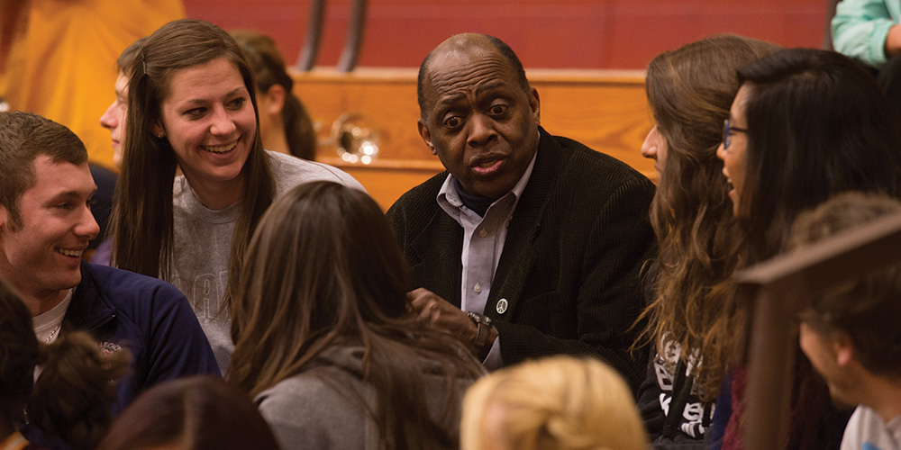 Tony Brown visits with students at a Hesston College basketball game.