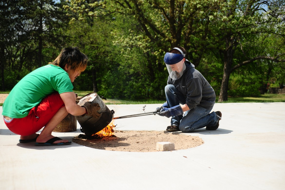 Hesston College ceramics instructor Hanna Eastin (right) and a student work on a raku firing of ceramics pieces. Eastin will instruct a week-long ceramics camp June 16 to 20 at Hesston College for young local artists to learn the basics of the art.