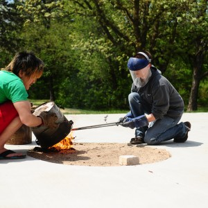 Hesston College ceramics instructor Hanna Eastin (right) and a student work on a raku firing of ceramics pieces.