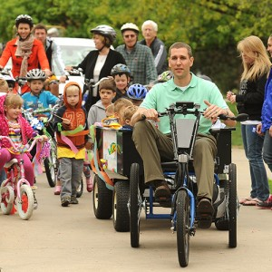 Mark Landes, Hesston College vice president of Finance and Auxiliary Services pulls a wagon of children from the college's preschool on a solar-charged personal activities vehicle to lead the Earth Day parade featuring alternative transportation options.