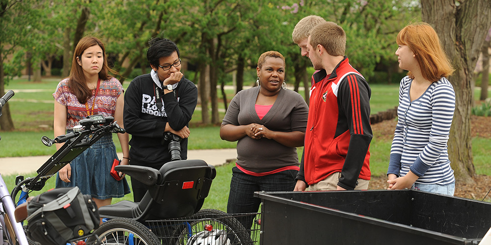 Natural science instructor Marelby Mosquera (third from left) talks with a group of students about the solar-charged personal activities vehicle built by students in the college's Physics II course.