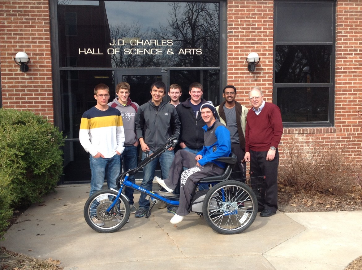 Hesston College Physics II students display the solar powered personal activities vehicle they built as a class project during the spring 2014 semester. The trike will be on display and available for test rides during the college's Earth Day celebration focusing on transportation alternatives from 10 a.m. to 2 p.m., April 24. Pictured from left are Tyler Roth (Canby, Ore.), Drew Hostetler (Goshen, Ind.), Phillip Horning (Ephrata, Pa.), Jerek Shoemaker (Newton, Kan.), Trevon Mast (Weatherford, Okla.), Scott Cooper (Sand Springs, Okla.), Awah Hammad (Khartoum, Sudan) and instructor Nelson Kilmer.
