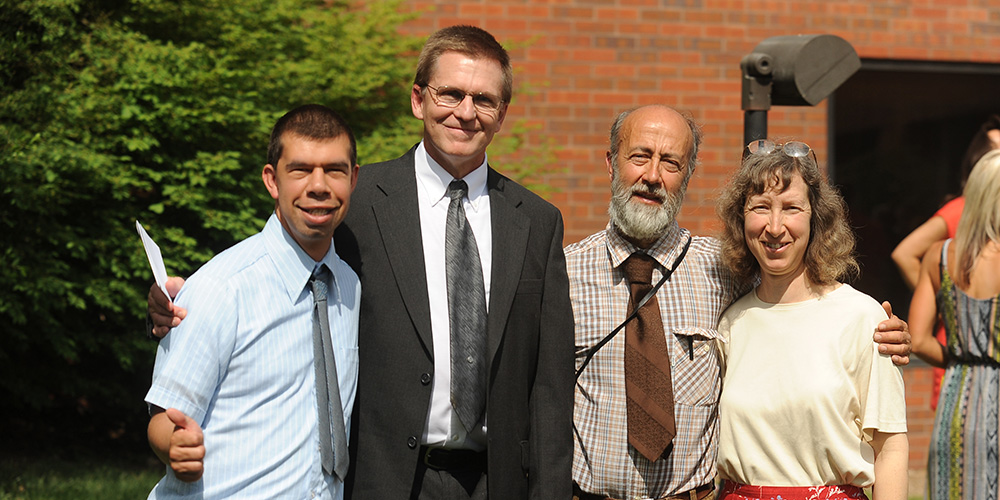 Simon Zehr (left) celebrates his graduation with his academic advisor Russ Gaeddert (second from left) and his parents Dennis Zehr and Ellen Davis-Zehr.