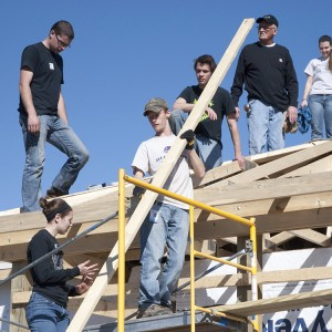 A group of Hesston College students and other volunteers work on the roof of a house in Pilger, Neb., during the college's spring break.