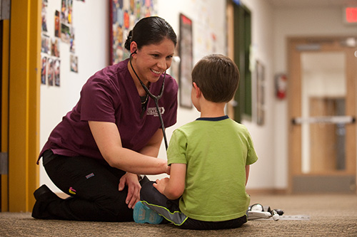 Dra Aguilar '16 (Wichita, Kan.) listens to a child's heartbeat at the Hesston Intergenerational Child Development Center.
