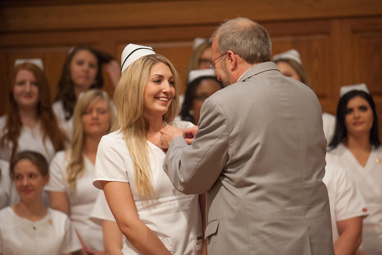 Taylor Schrag '15 (Moundridge, Kan.) recieves her nursing pin from faculty member Gregg Schroeder '86 during Nursing Pinning May 10.
