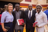 Alpha Mavungu Kivuvu is congratulated by education instructor Marissa King '05, social science instructor and artist in residence Tony Brown and Rince Longo Kabondo.