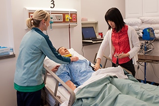 Former nursing students practice on a simulated patient in the on-campus Newton Medical Center nursing simulation lab.