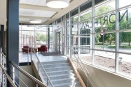 The front entry of the Northlawn Center for Performing Arts Education is an addition to the existing building, providing a welcoming entrance and access to the lower level. The glass front lets natural light into the building and offers an expansive view of campus.