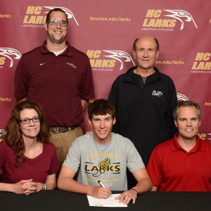 Kyle Stucky signs a letter of intent to run cross country for Hesston College.